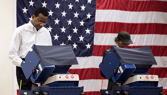 People voting in front of an American flag