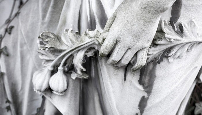 stone sculpture hand holding a poppy